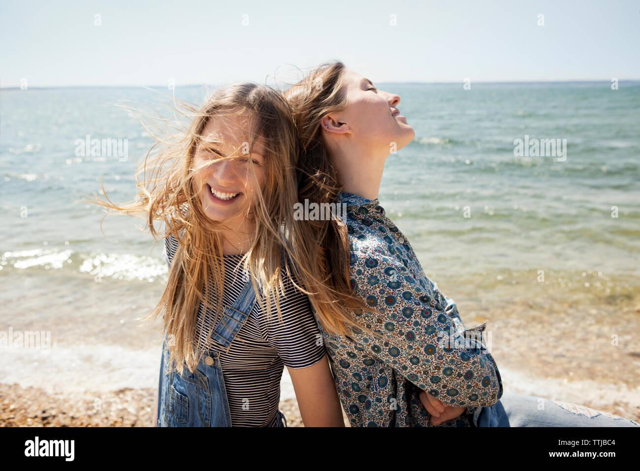 Happy amici in piedi di schiena contro la spiaggia Immagini Stock
