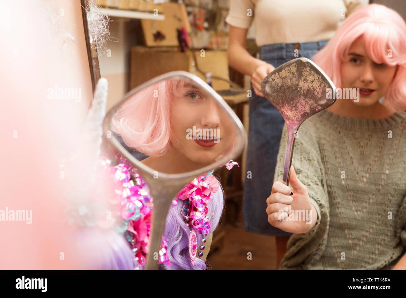 Donna che indossa parrucca rosa mentre guardando lo specchio a mano nel negozio di abbigliamento Immagini Stock