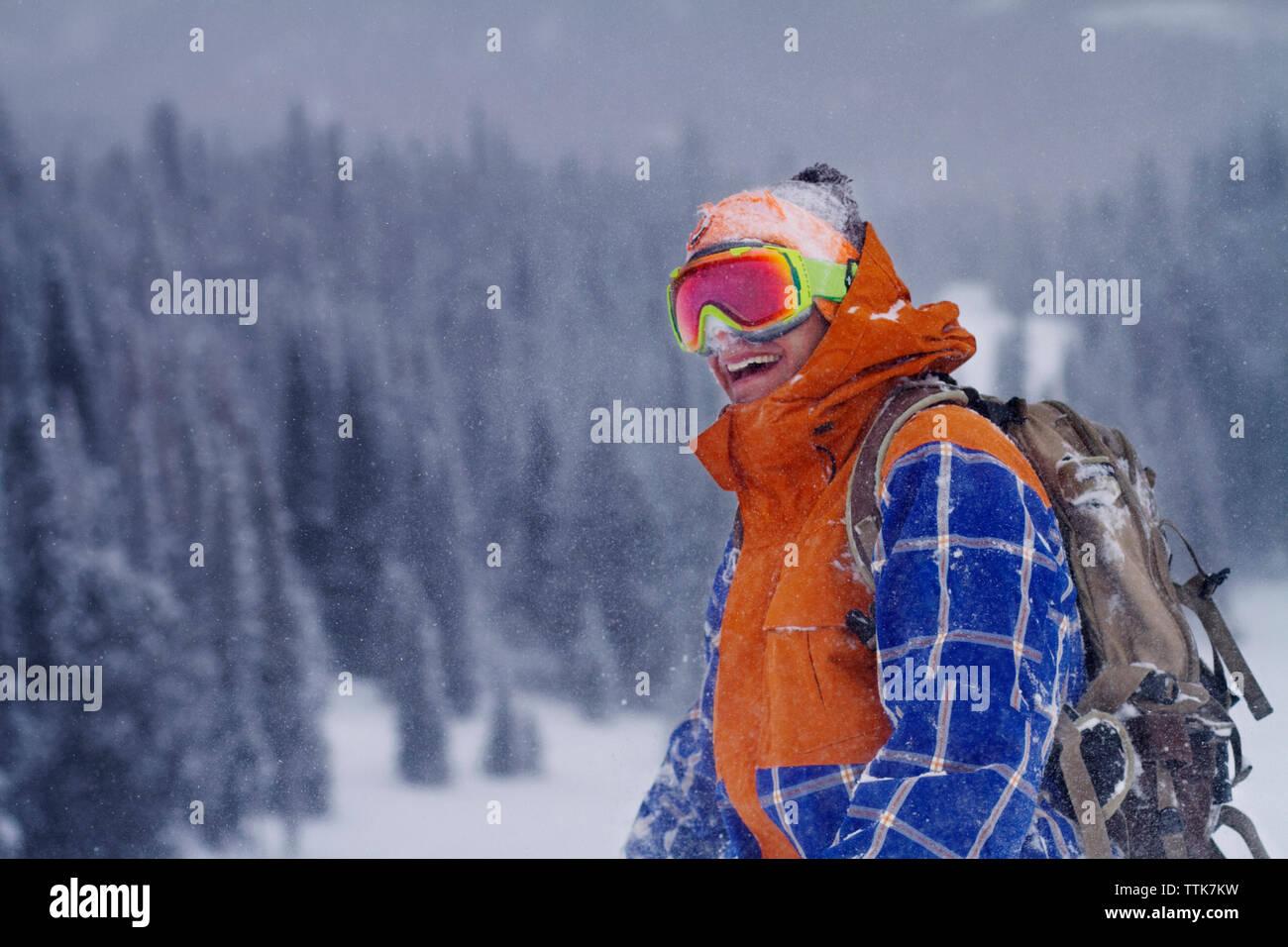 Uomo felice indossando occhiali da sci in piedi sul campo durante la nevicata Immagini Stock