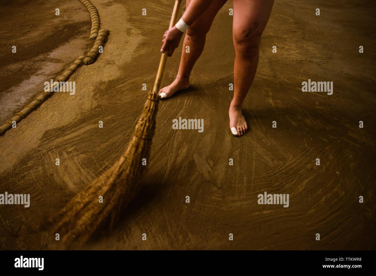 Sezione bassa di wrestler campo di spazzamento in sumo beya Immagini Stock
