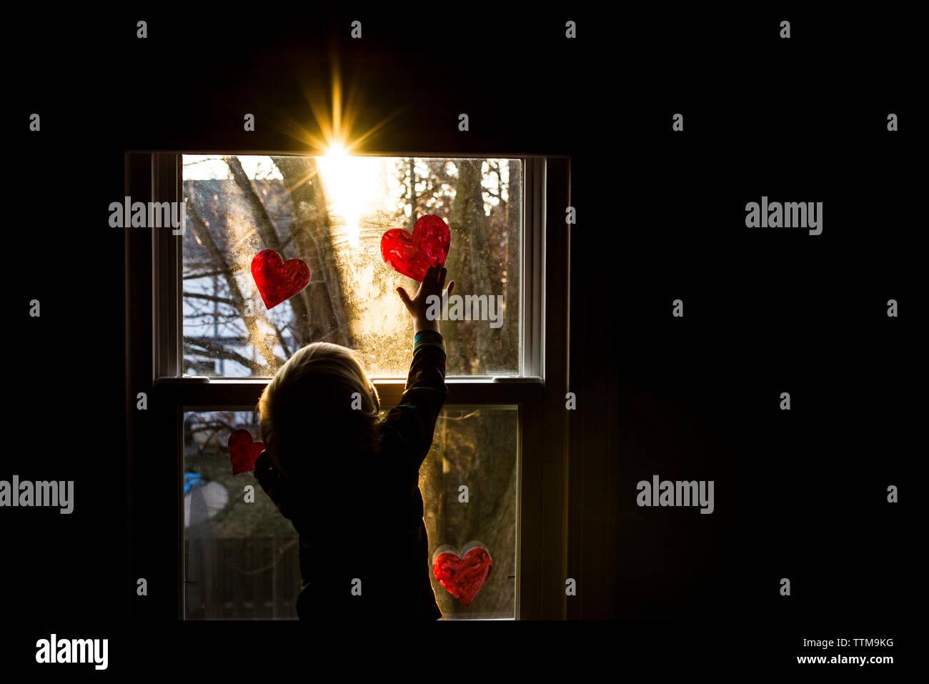 Vista posteriore del ragazzo di incollaggio forme di cuore sulla finestra a casa Immagini Stock