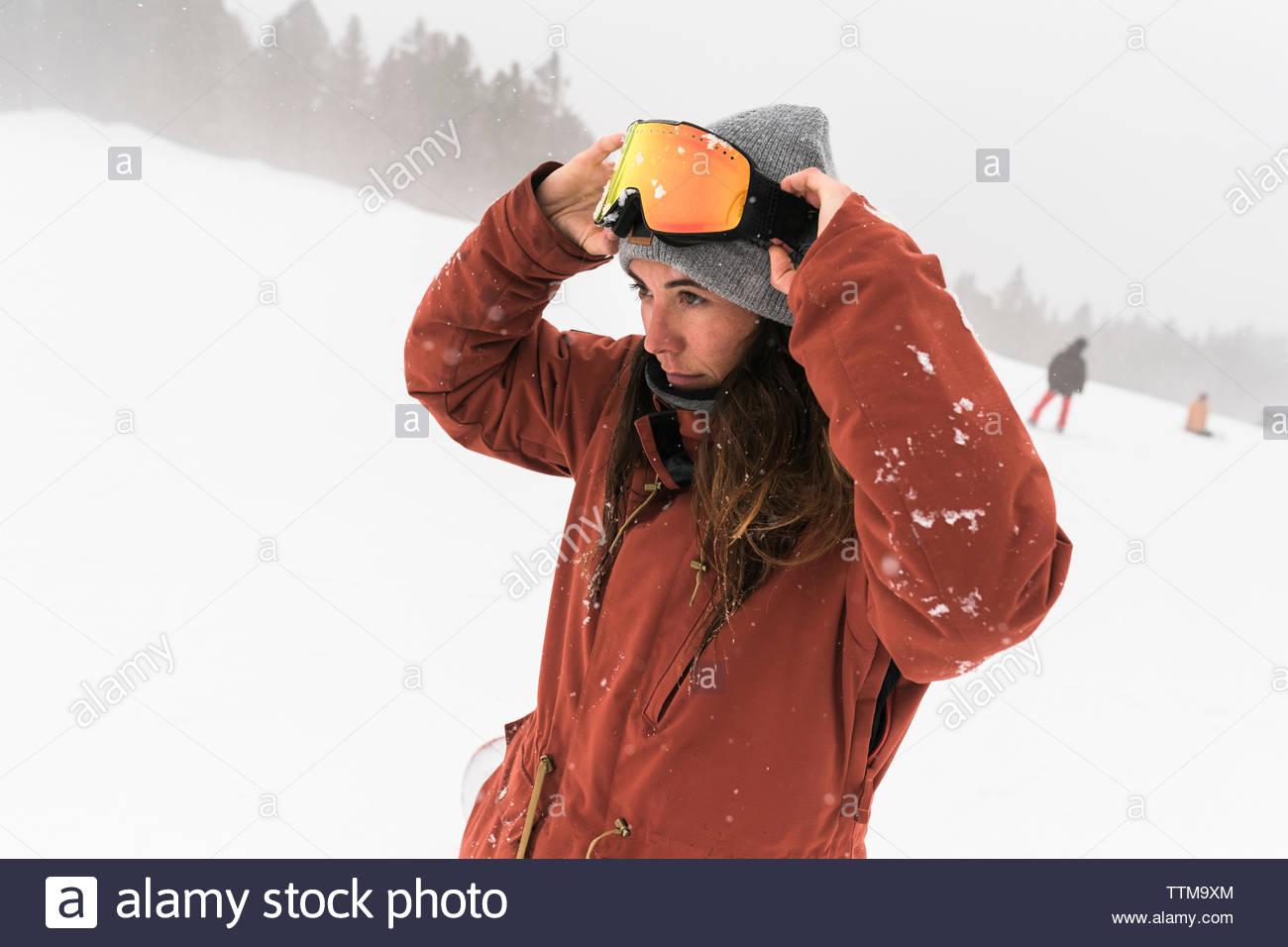 Donna che indossa gli occhiali da sci mentre si sta in piedi sul campo nevoso durante la nebbia meteo Immagini Stock
