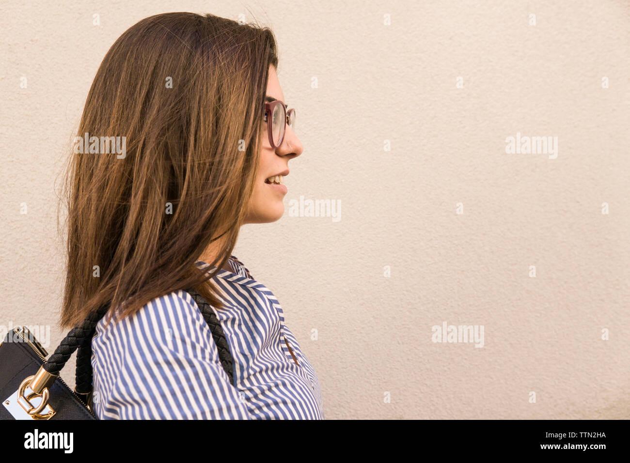 Vista laterale della ragazza adolescente con capelli castani dalla parete Immagini Stock