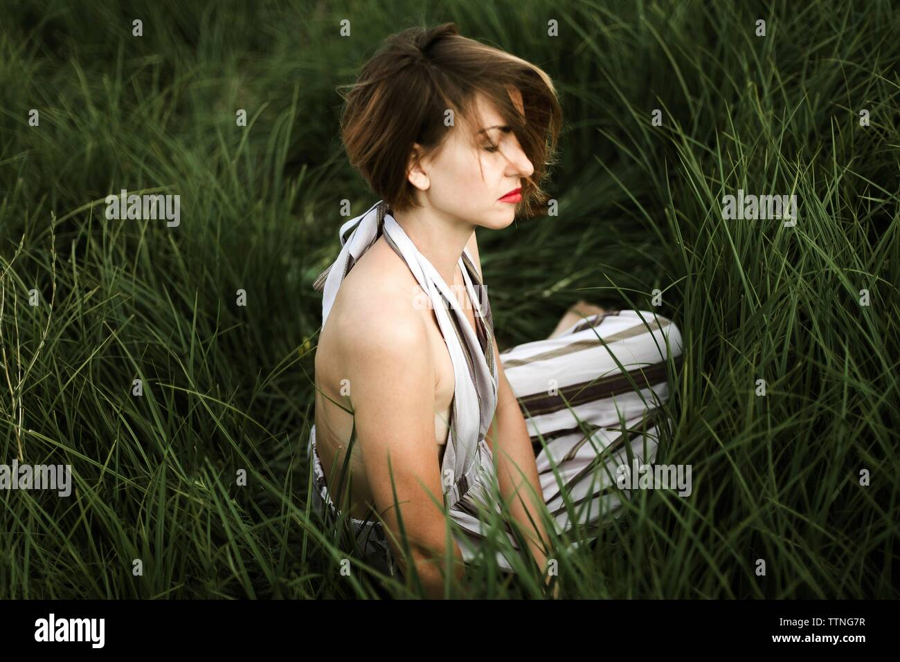 Ritratto di donna bella nel vestire rilassante sul campo erboso Foto Stock
