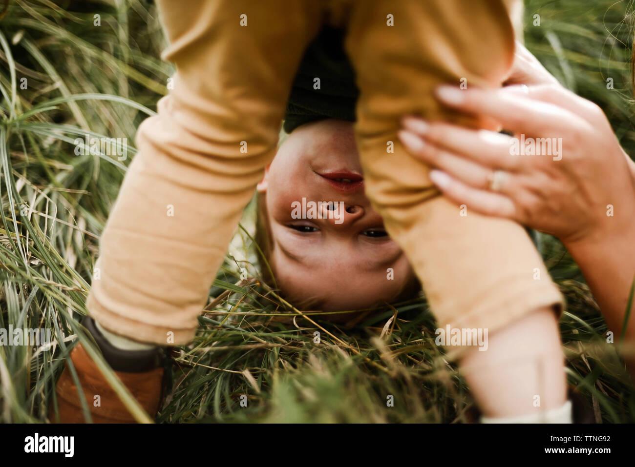 Ritratto di un ragazzino con la testa in giù a giocare al di fuori in estate Foto Stock