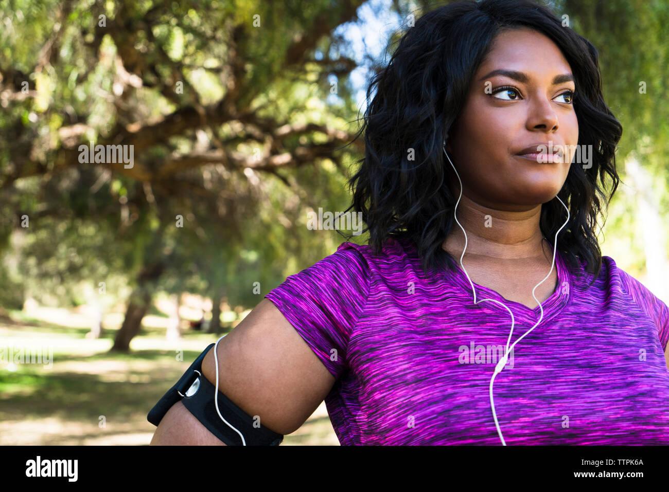 Fiducioso donna che guarda lontano mentre si ascolta la musica al parco Immagini Stock
