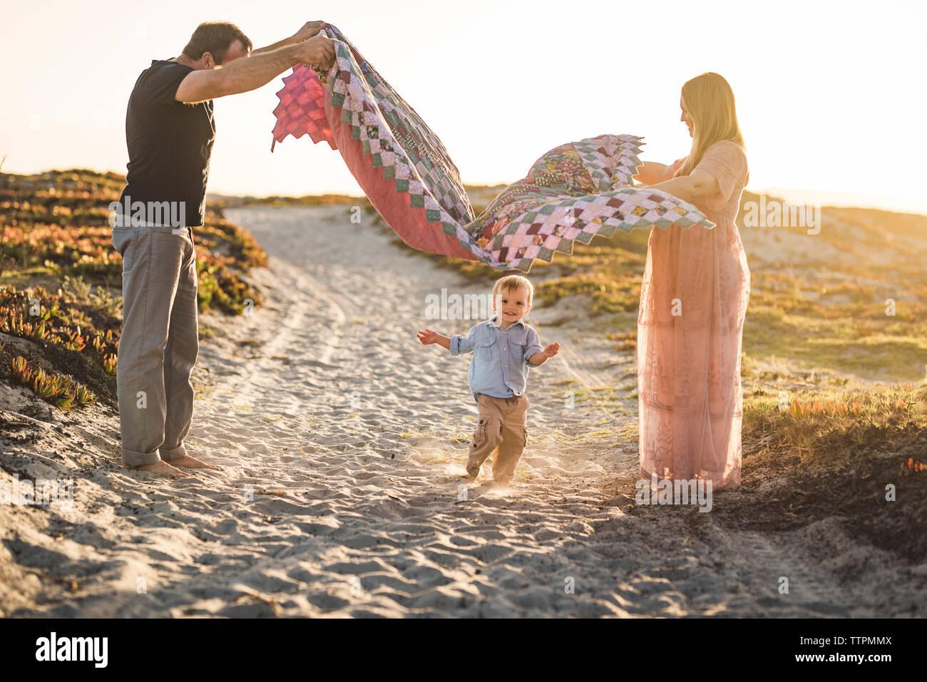 Vista laterale dei genitori tenendo coperta più carino figlio in esecuzione sulla sabbia in spiaggia contro il cielo chiaro durante il tramonto Foto Stock