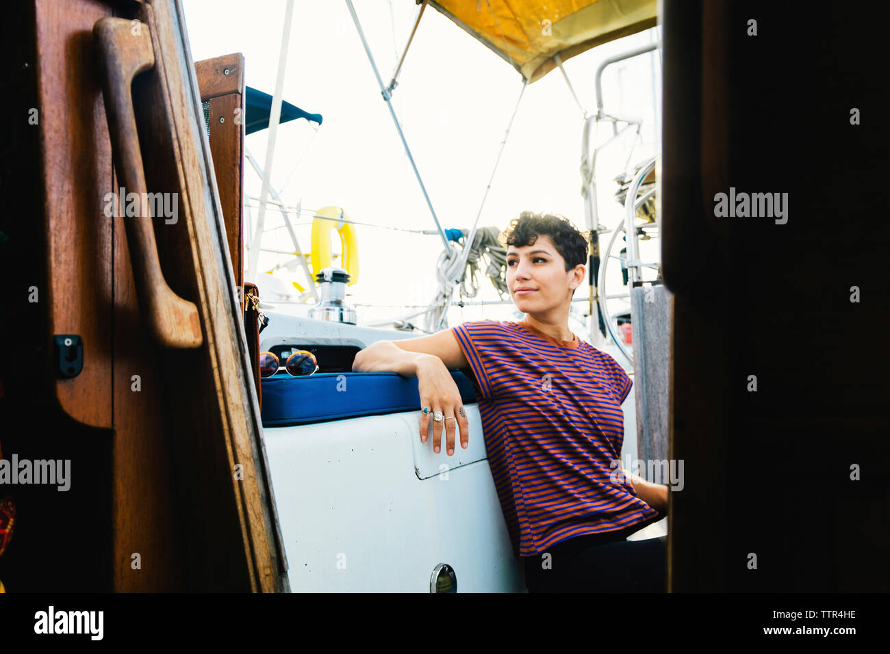 Premurosa donna che guarda lontano mentre è seduto in barca contro il cielo visto attraverso la finestra Foto Stock