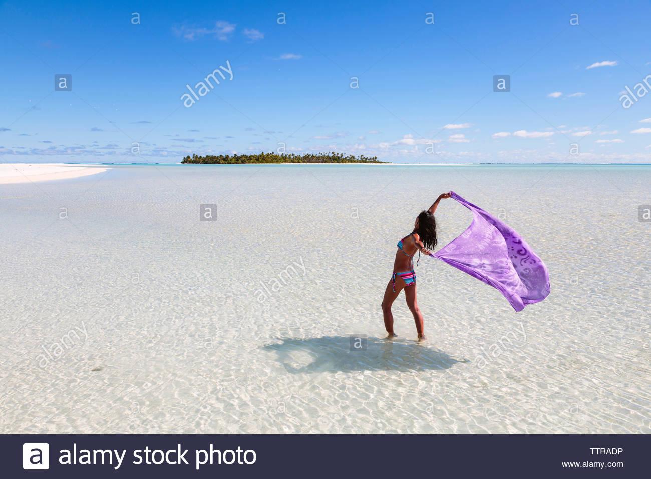 Donna che mantiene sarong permanente, mentre in Laguna Aitutaki contro il cielo blu Immagini Stock