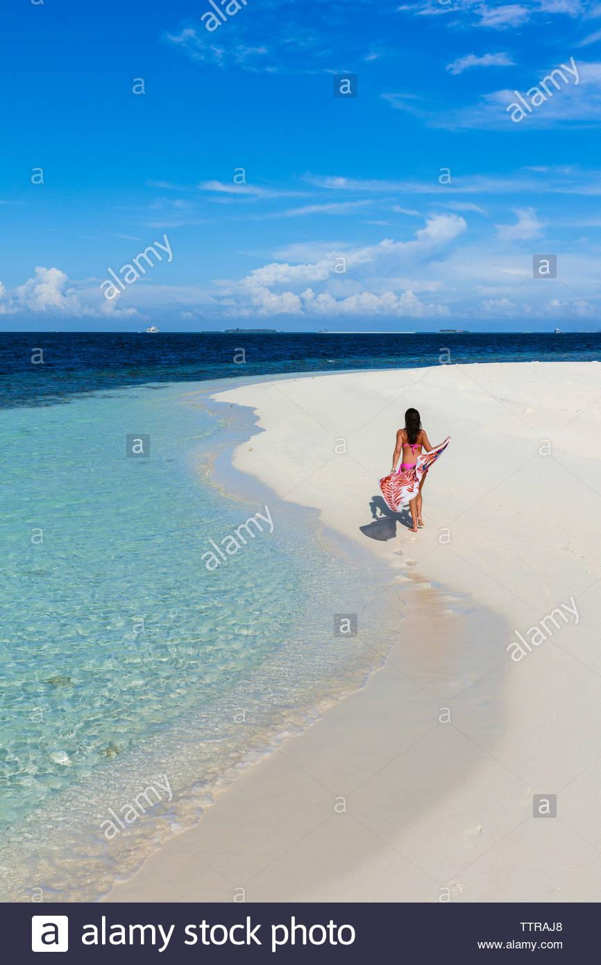 Vista posteriore della donna con sarong a piedi di spiaggia contro il cielo blu durante la giornata di sole Immagini Stock