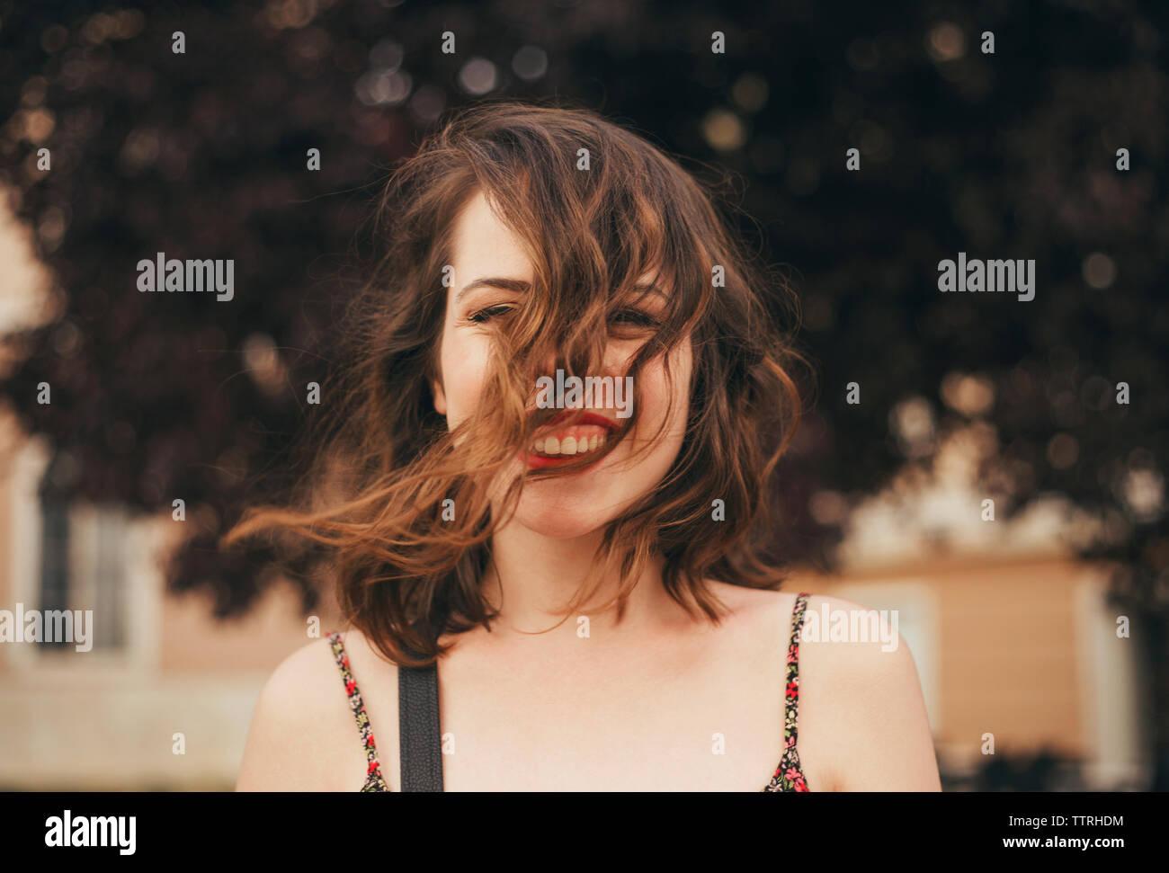 Ritratto di felice giovane donna con capelli tousled all'aperto Immagini Stock