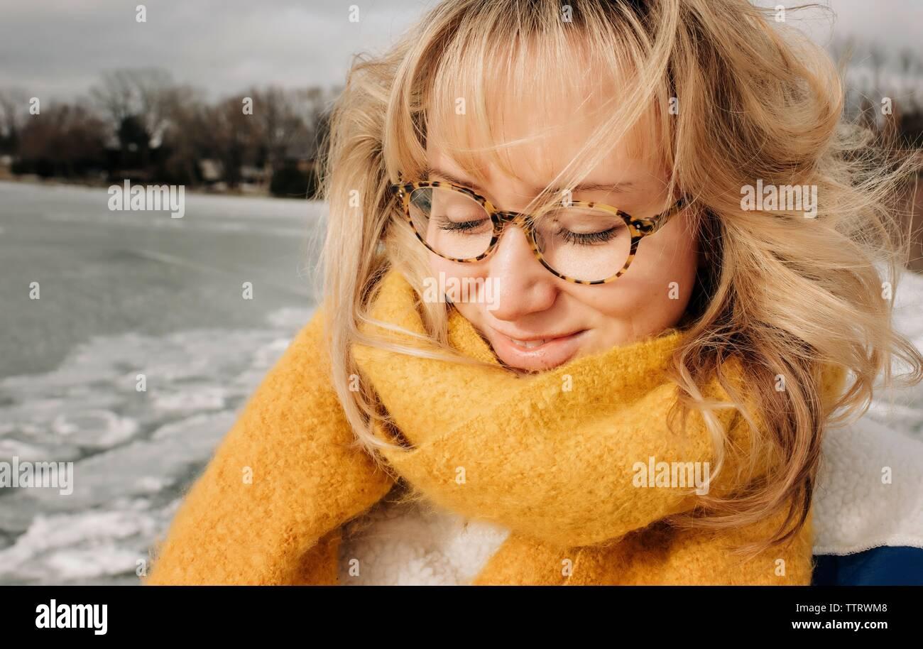 Ritratto di donna bionda con gli occhiali a sorridere mentre in spiaggia Foto Stock