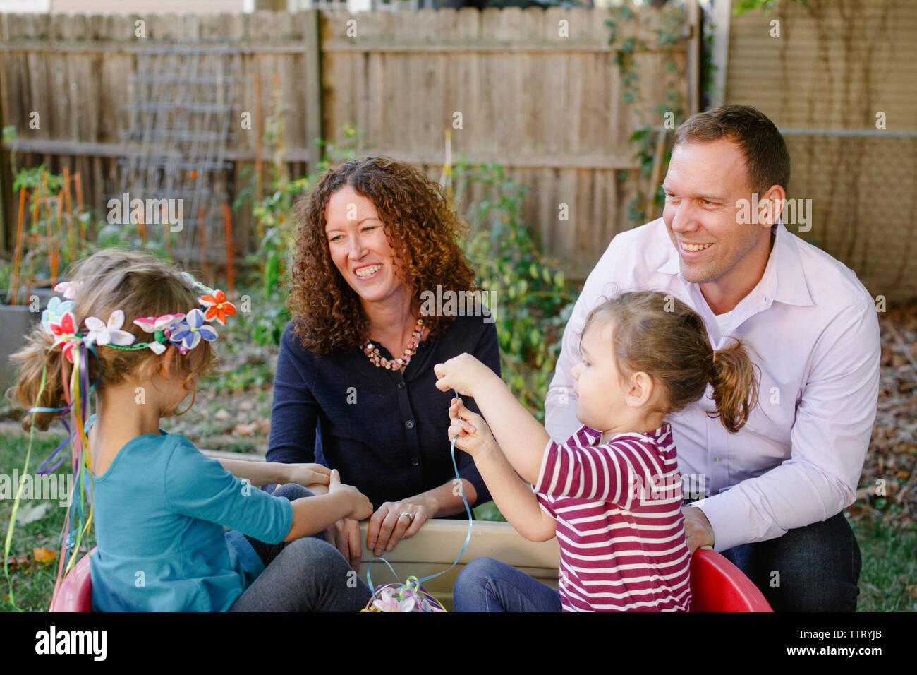Due bambine giocare mentre i loro genitori guarda con affetto in Foto Stock