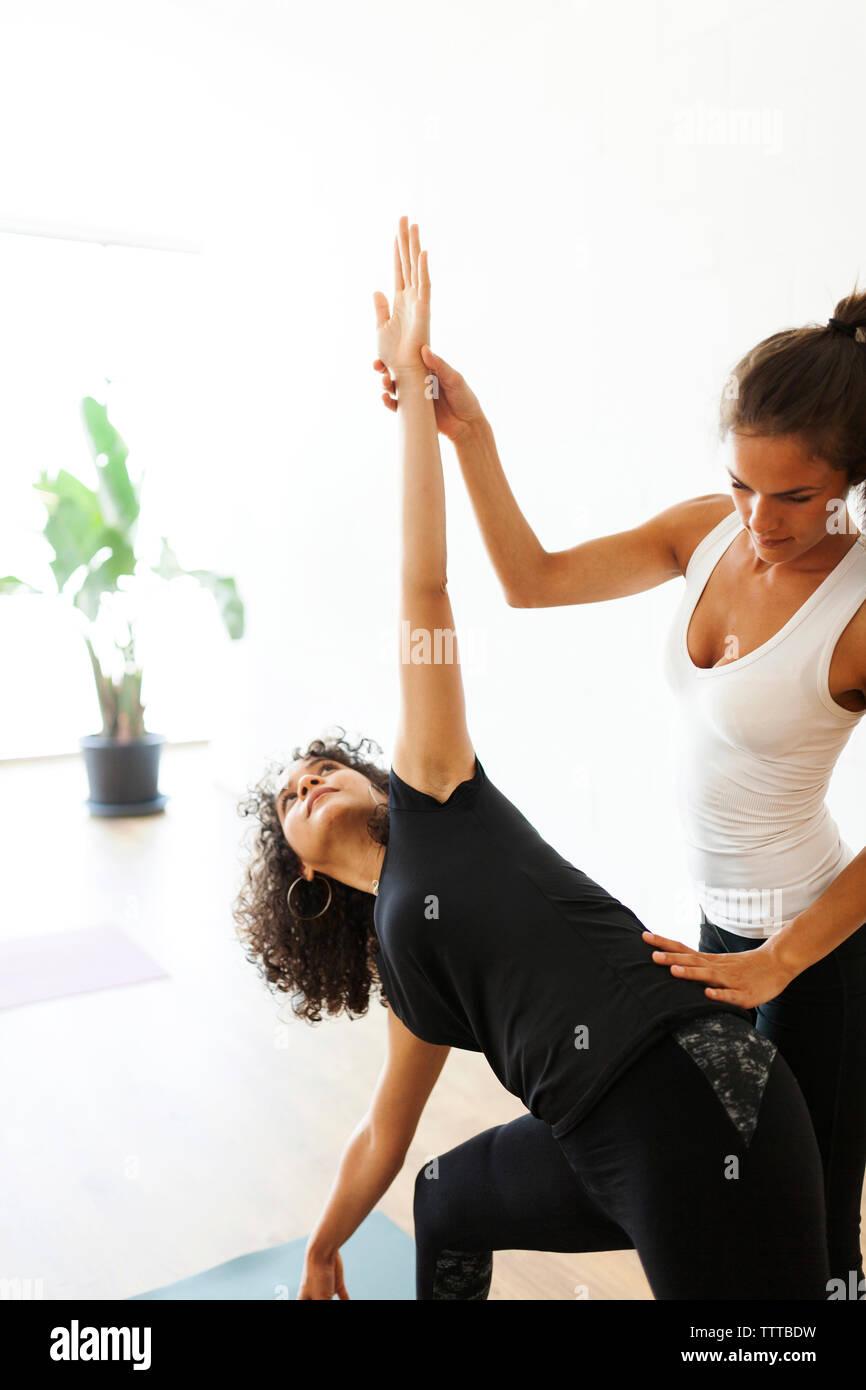 Istruttore Yoga aiutare la donna a esercitare presso studio di yoga Foto Stock