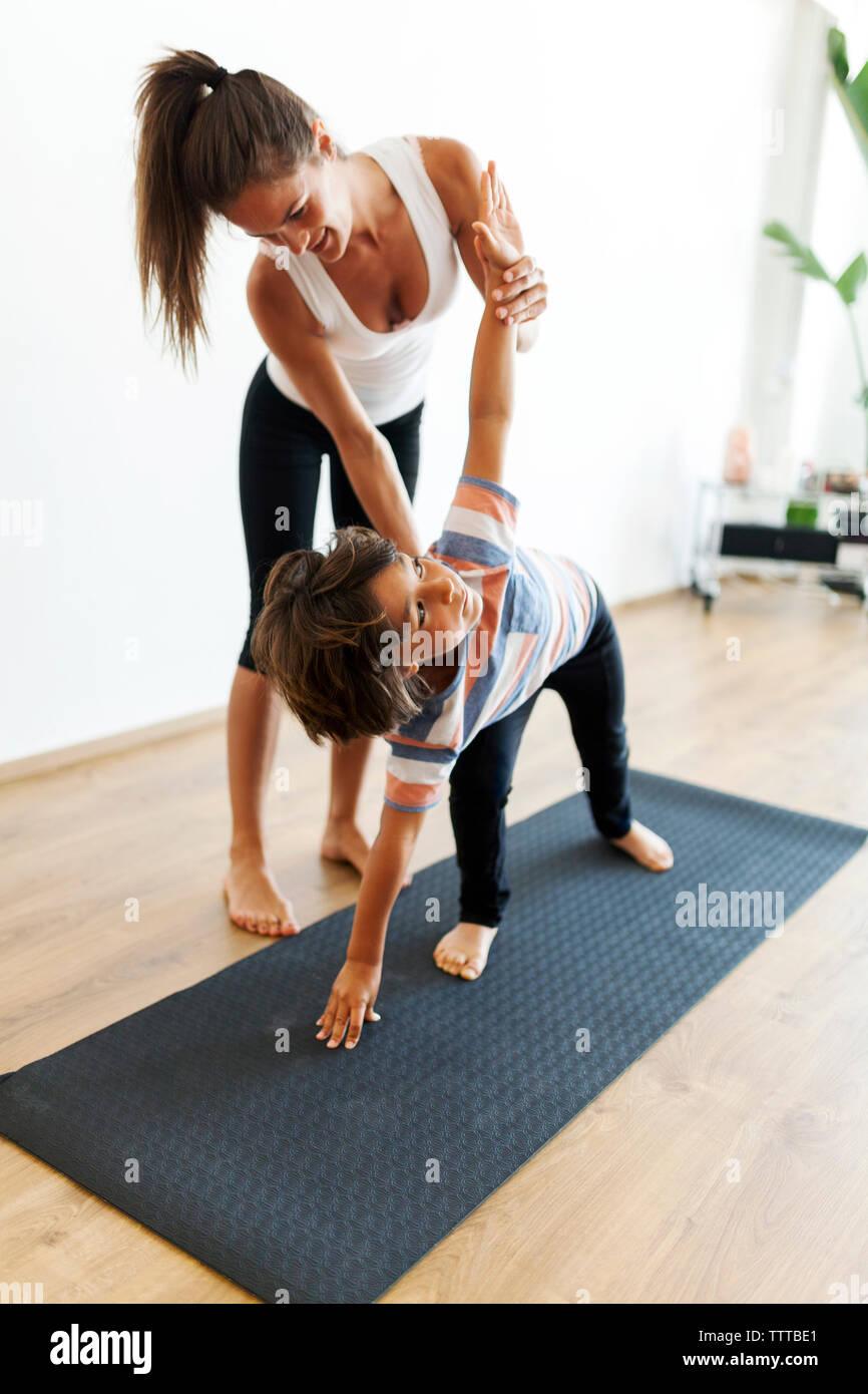 Lunghezza completa di istruttore yoga assistere boy in esercizio a studio di yoga Foto Stock
