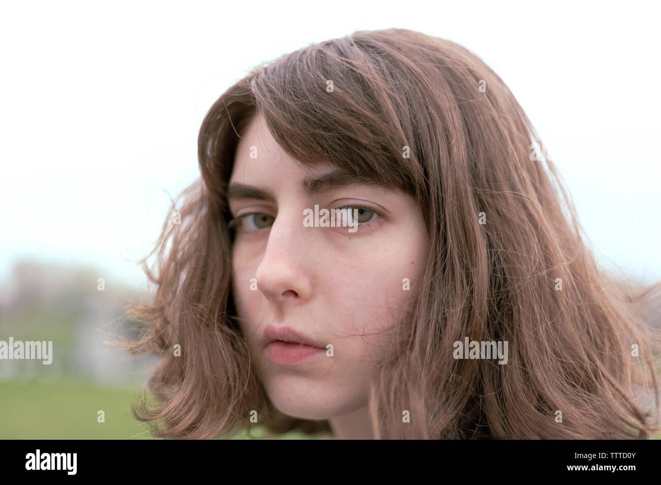 Close-up verticale di grave giovane donna con capelli castani Immagini Stock