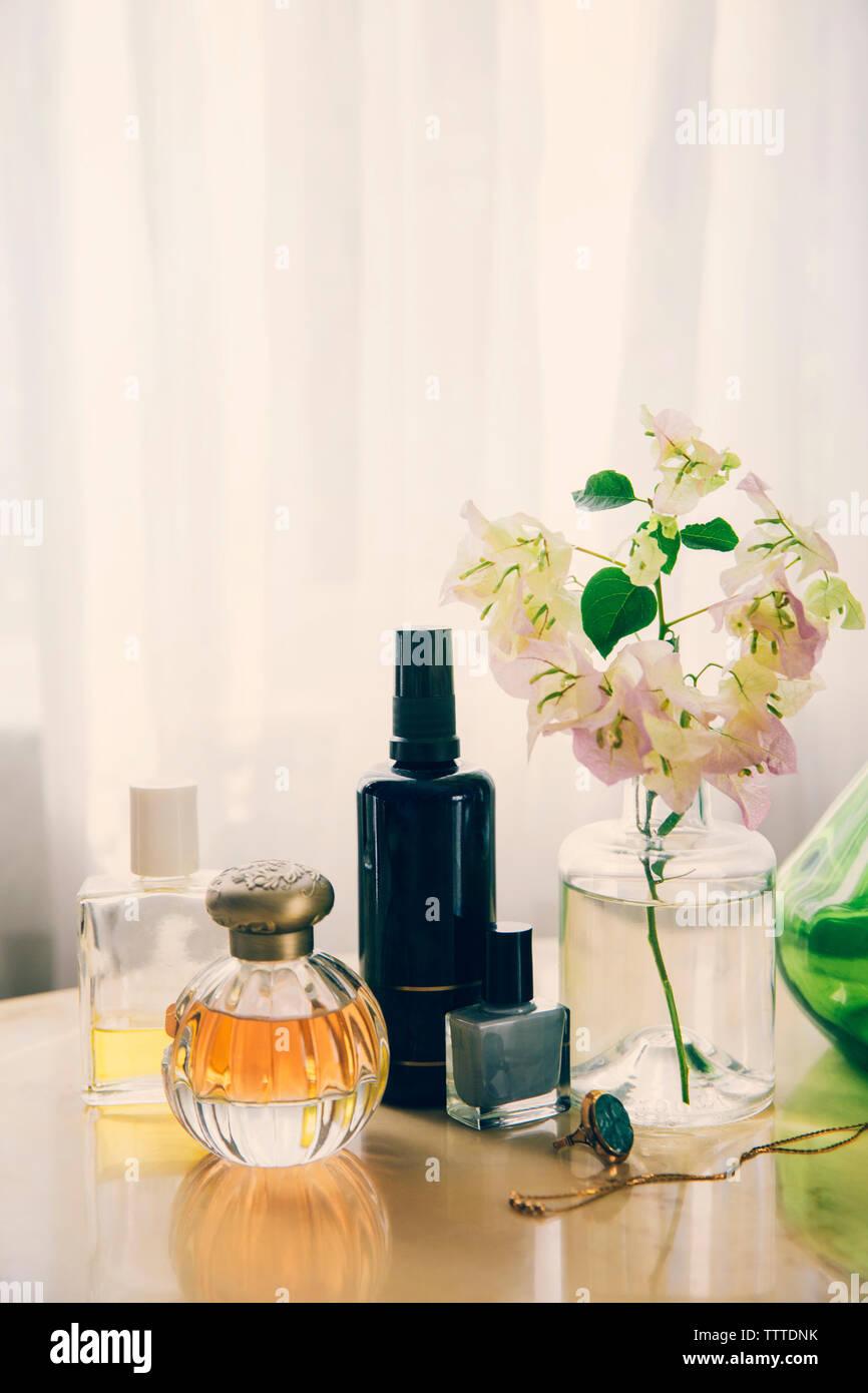 Prodotti di bellezza con gioielli dal vaso di fiori disposti sul tavolo Foto Stock