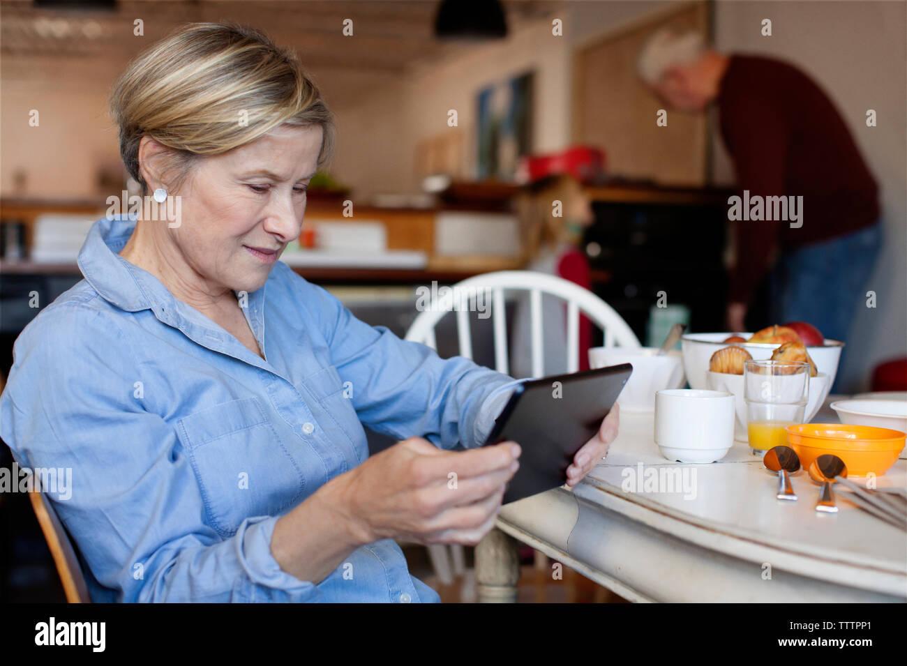 Donna che utilizza computer tavoletta mentre il marito in piedi con la nipote di sfondi Immagini Stock