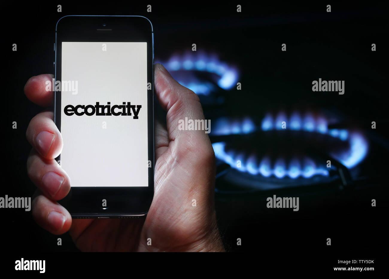 Un uomo che guarda il logo del sito web per l'energia azienda Ecotricity sul suo telefono cellulare nella parte anteriore della sua cucina a gas (solo uso editoriale) Immagini Stock