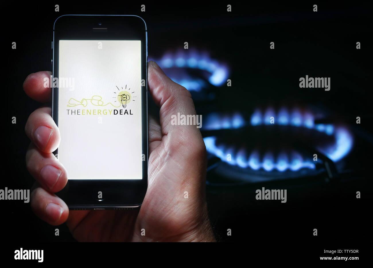 Un uomo che guarda il logo del sito web per azienda di energia l'energia trattare sul suo telefono cellulare nella parte anteriore della sua cucina a gas (solo uso editoriale) Immagini Stock