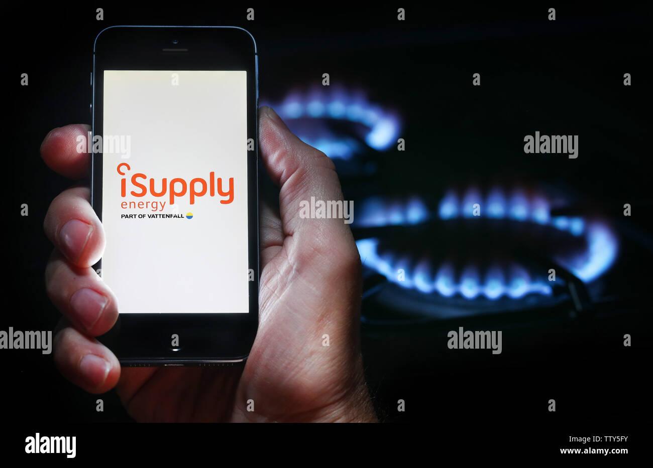Un uomo che guarda il logo del sito web per la società energetica iSupplyEnergy sul suo telefono cellulare nella parte anteriore della sua cucina a gas (solo uso editoriale) Immagini Stock