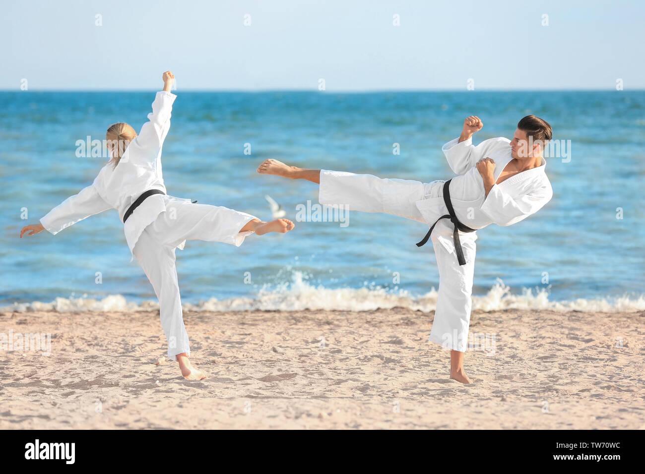 Giovane uomo e donna a praticare il karate all'aperto Immagini Stock