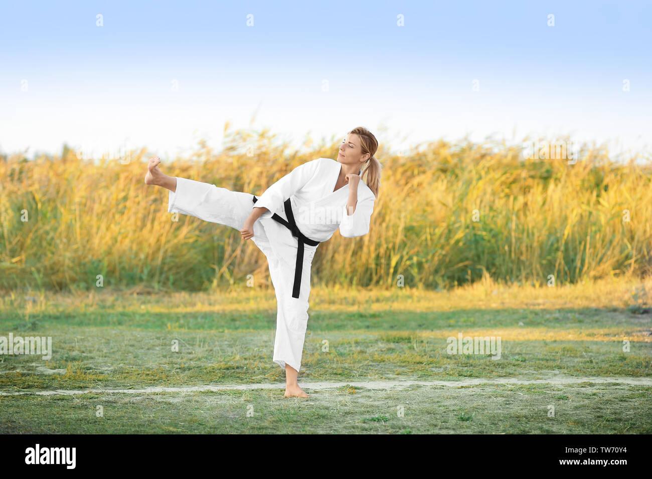 Giovane donna a praticare il karate all'aperto Immagini Stock