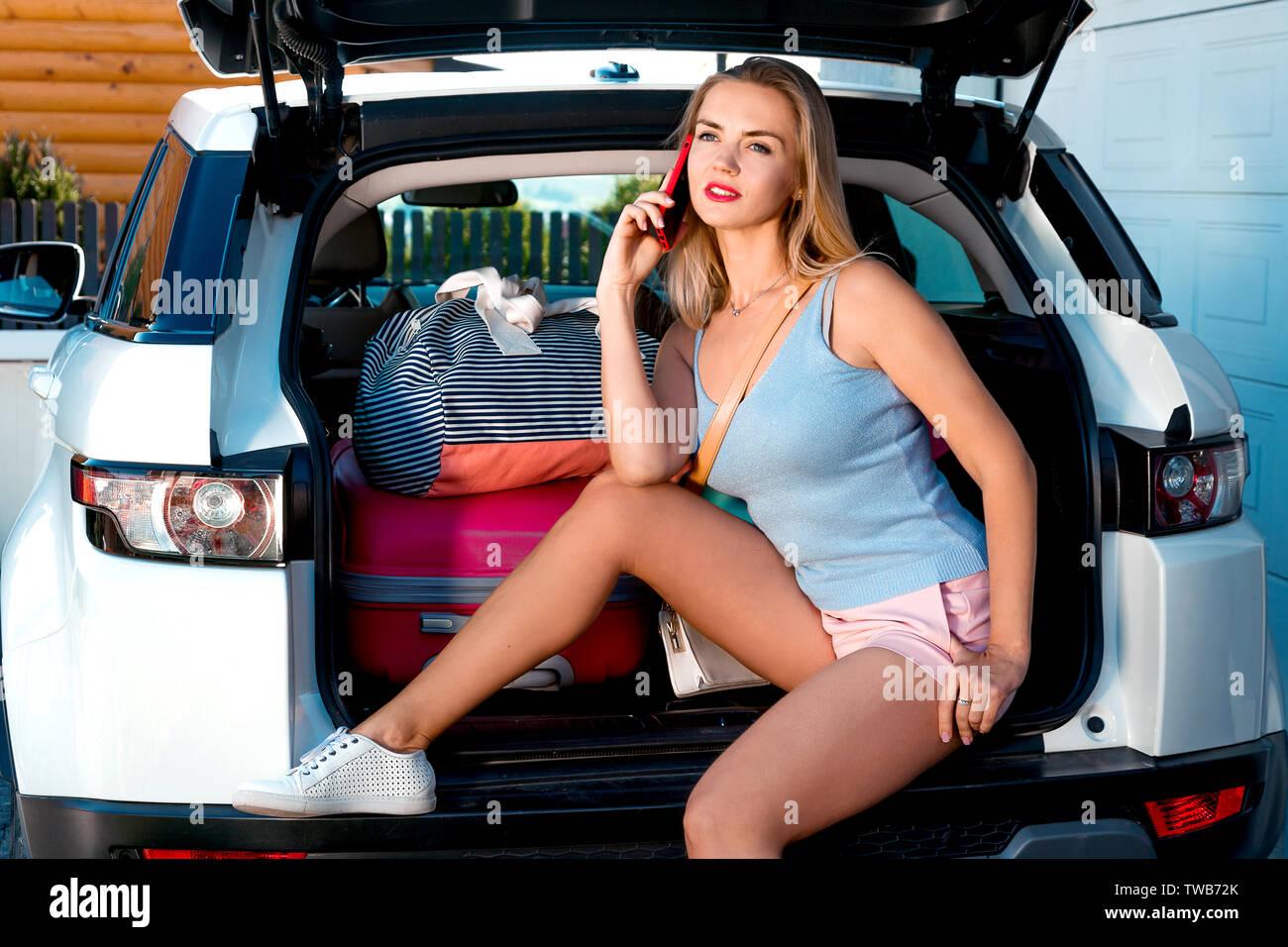 Giovane donna seduta nel retro della vettura con molte borse e valigie. Ragazza ridere seduto in aprire il bagagliaio di un auto e utilizza un telefono e una compressa di selezione Immagini Stock