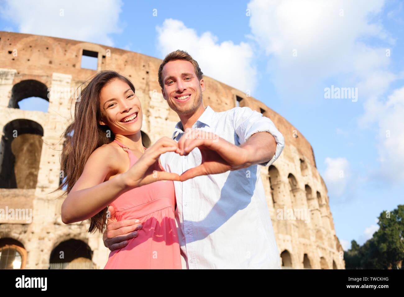 Viaggio Romantico giovane a Roma dal Colosseo, Italia. Felici gli amanti in luna di miele che mostra cuore sharped mani divertirsi nella parte anteriore del Colosseo. Amore e concetto di viaggio con multirazziale giovane. Foto Stock