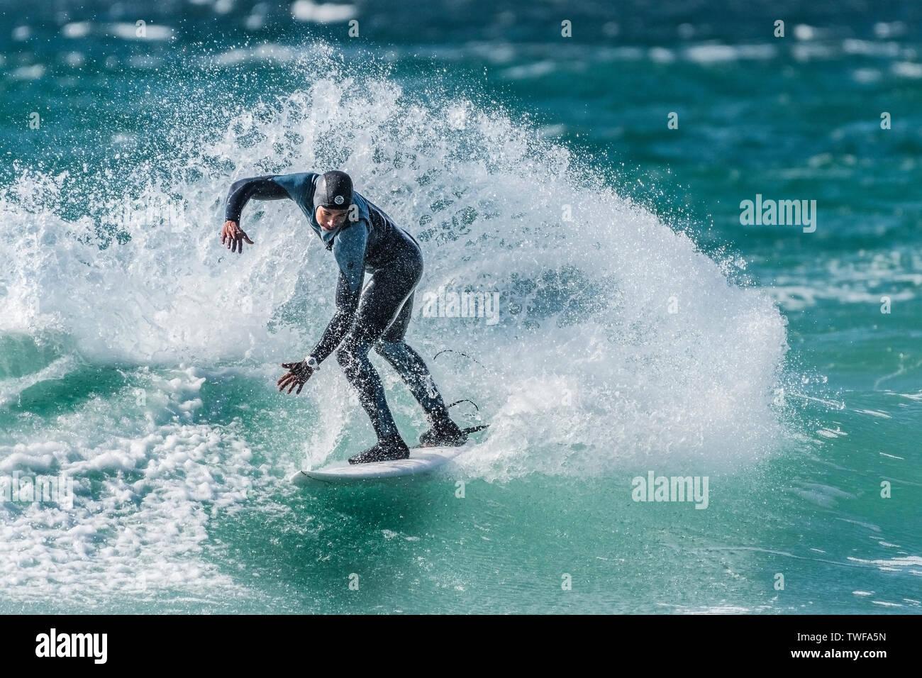 Un surfista di eseguire un trick a scatto a Fistral a Newquay in Cornovaglia. Immagini Stock