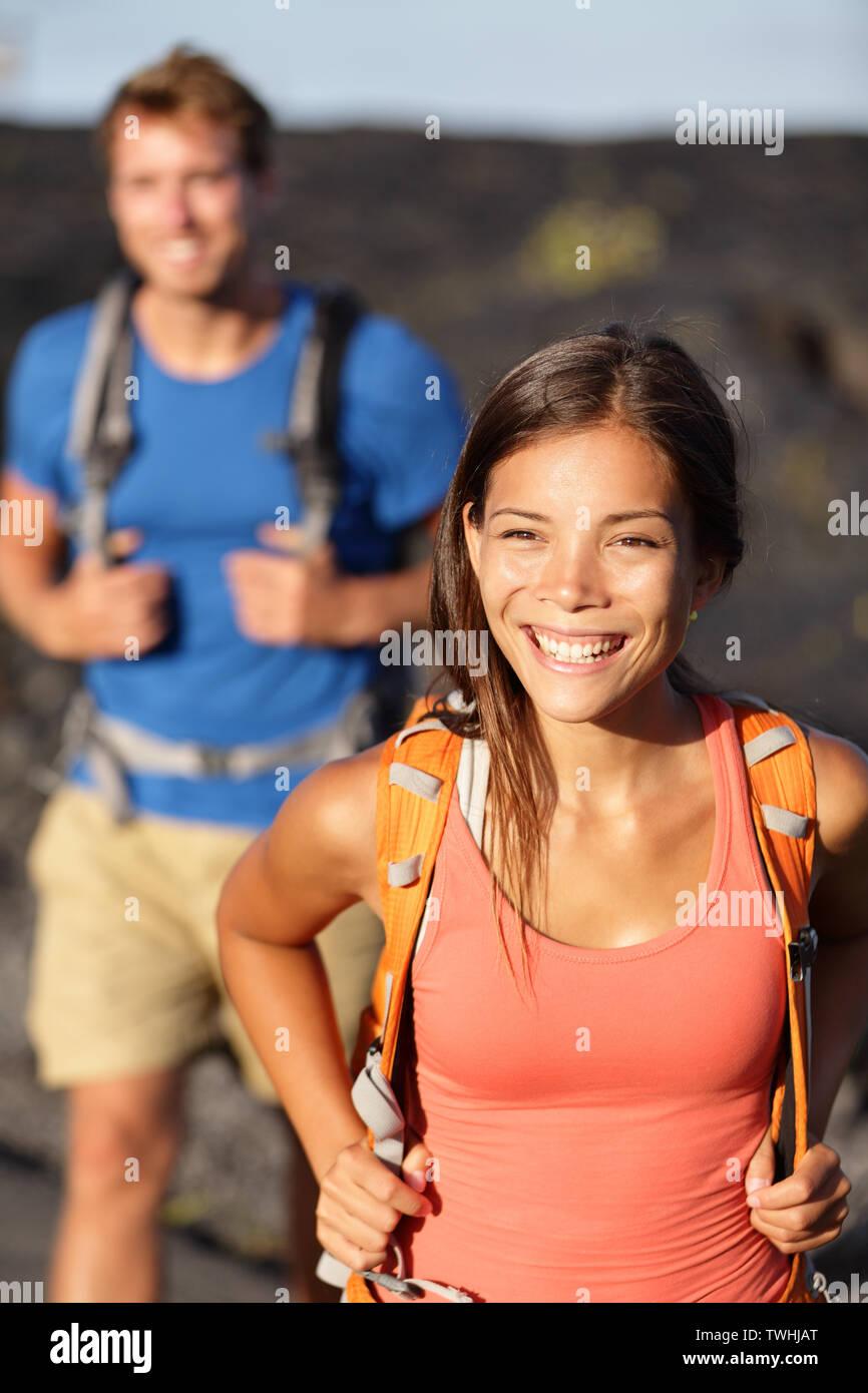 Escursionismo coppia - donna asiatica escursionista camminando sul campo lavico alle Hawaii. I turisti escursionisti sulla passeggiata vicino vulcano Kilauea intorno al Parco Nazionale dei Vulcani delle Hawaii, Stati Uniti d'America. Foto Stock