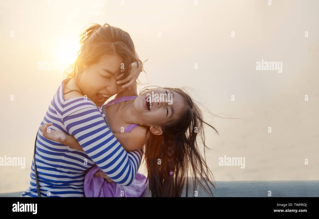 Bel momento con mamma e bambino giocare e abbraccio con il tramonto luce calda. amore insieme famiglia Foto Stock