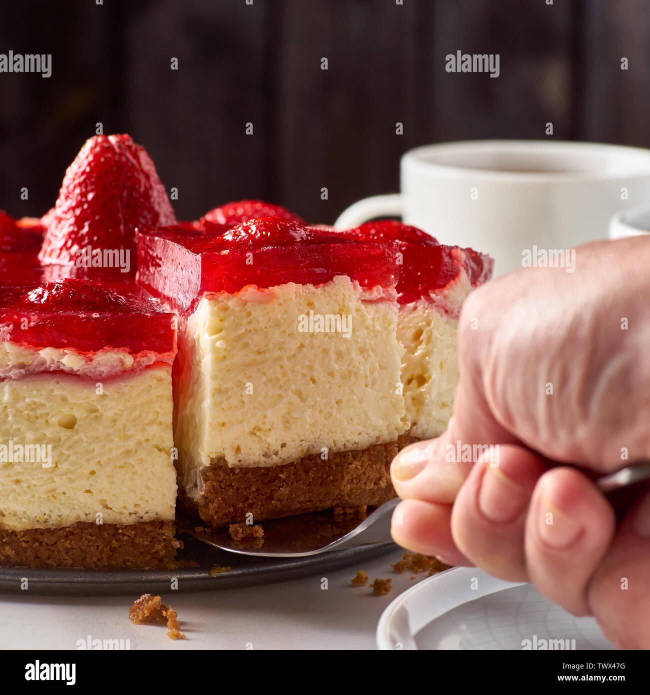 Mano sollevata pezzo di cheesecake con fragole Immagini Stock