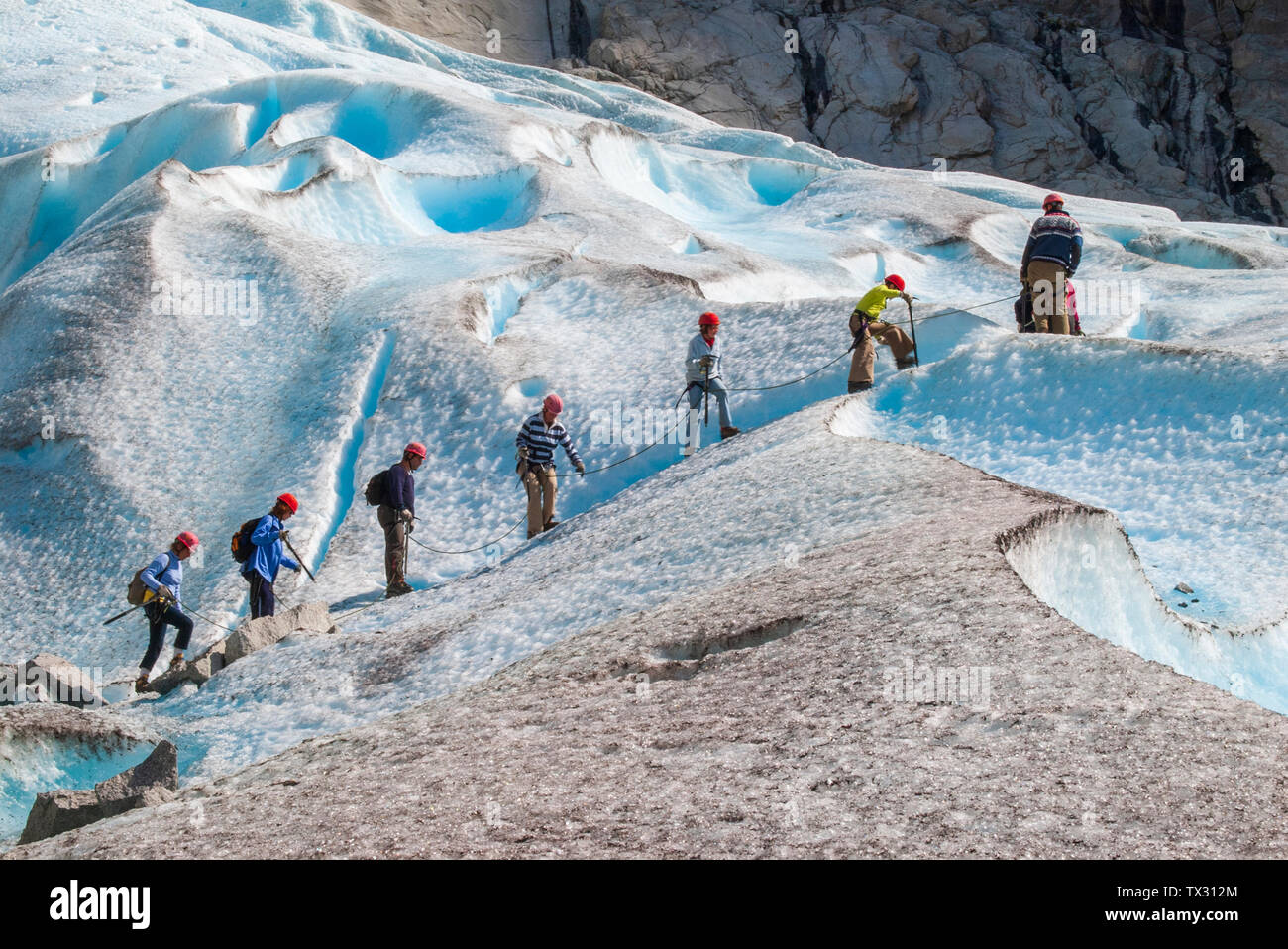 I turisti a camminare su un ghiacciaio guidato tour sul Ghiacciaio Briksdal in Norvegia Foto Stock