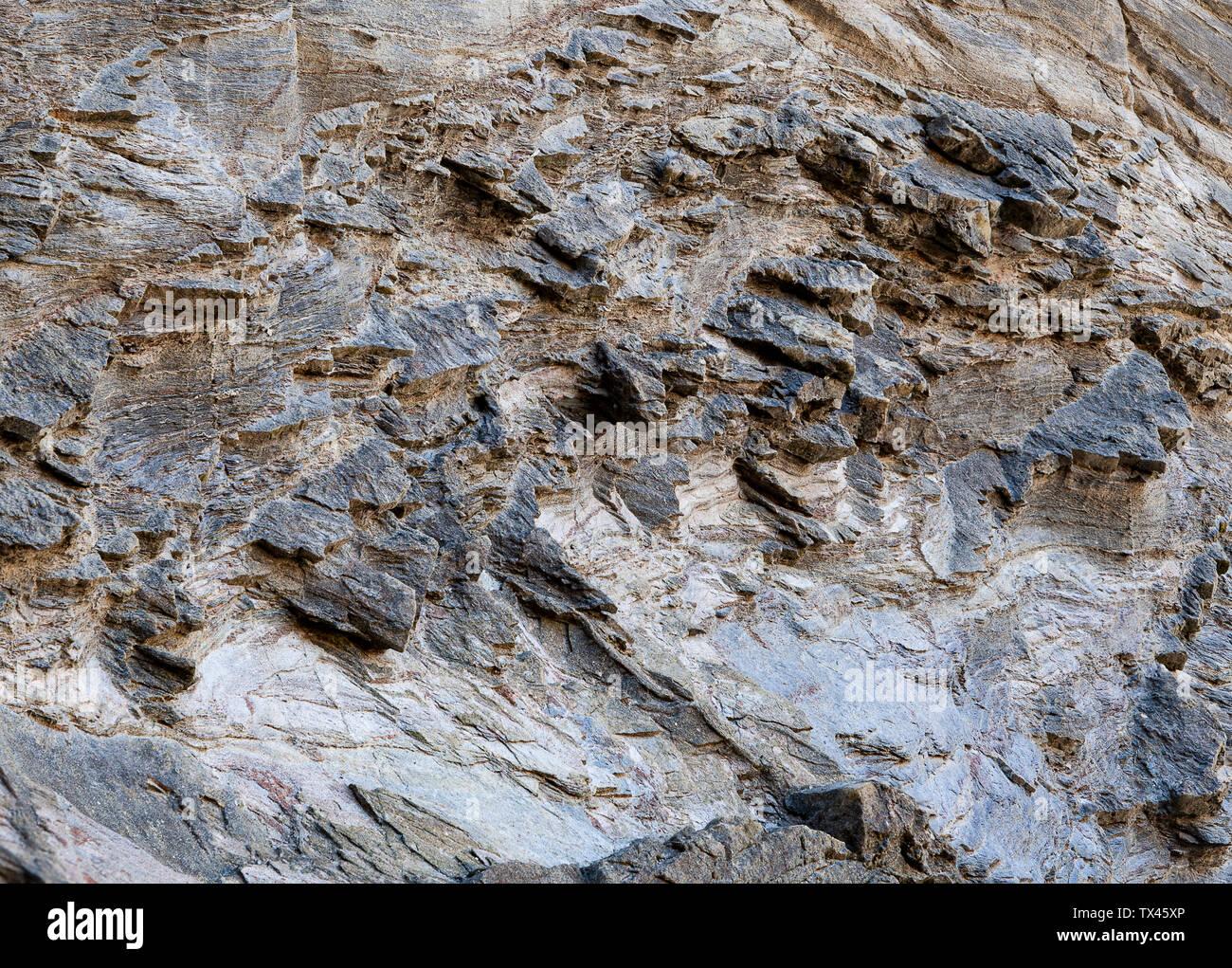 La superficie della parete rocciosa con durezze differenti in cui i pezzi di roccia più dura stare fuori formando slienties. Può essere utilizzato come sfondo. Foto Stock