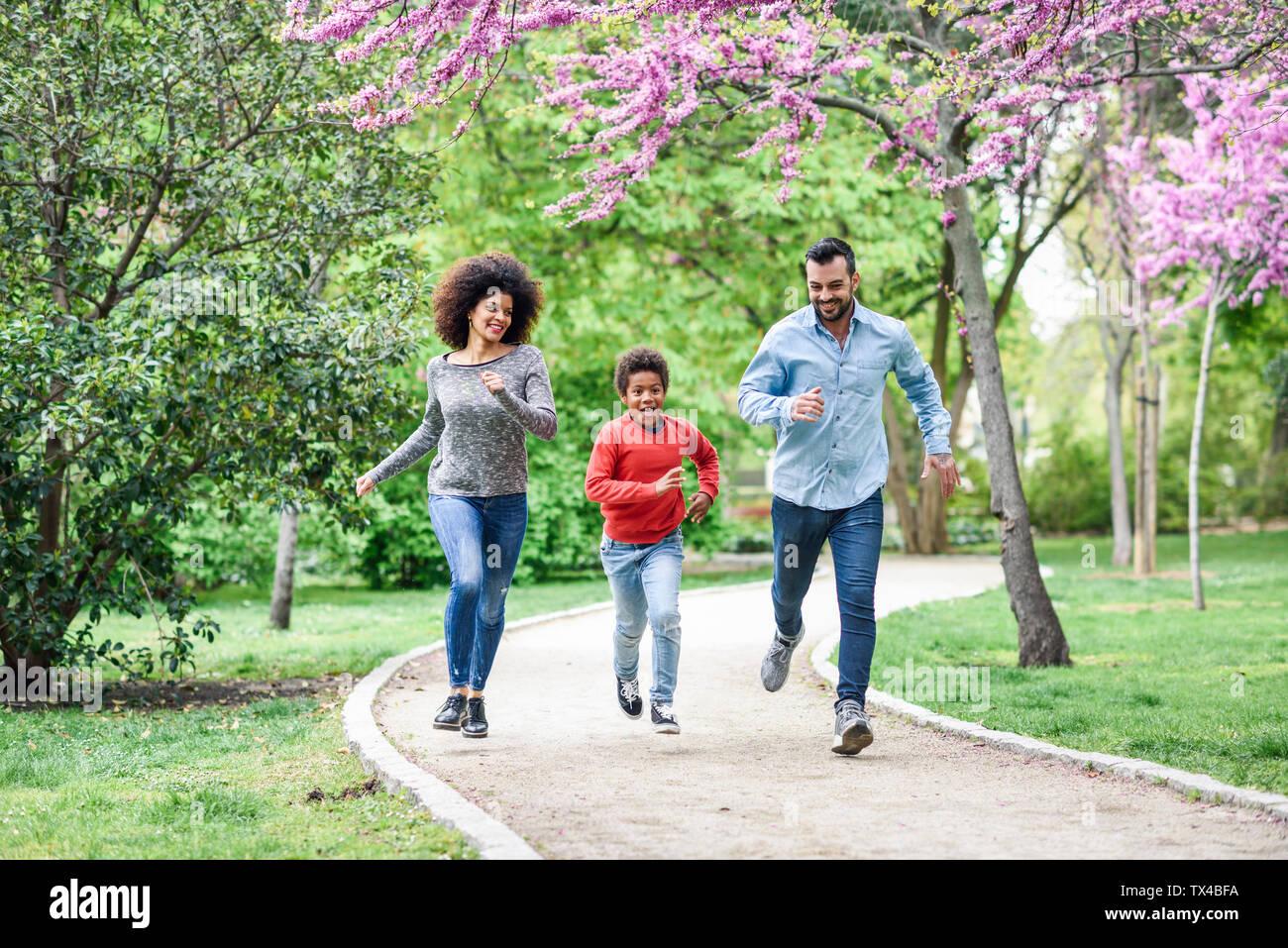 La famiglia felice correre e giocare in un parco Foto Stock