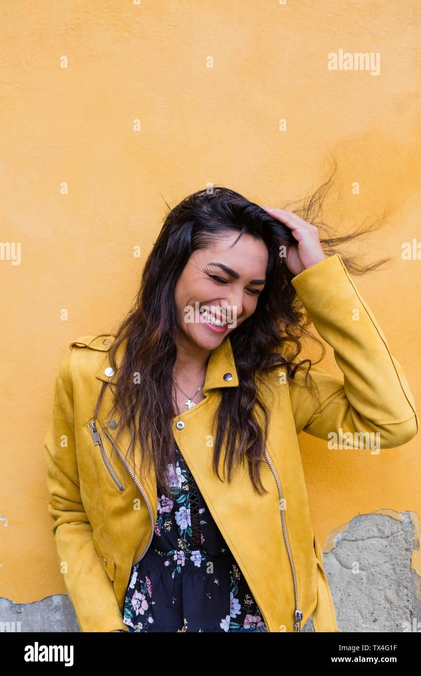 Ritratto di giovane donna ridere giallo da indossare giacca di pelle, mano nei capelli Foto Stock
