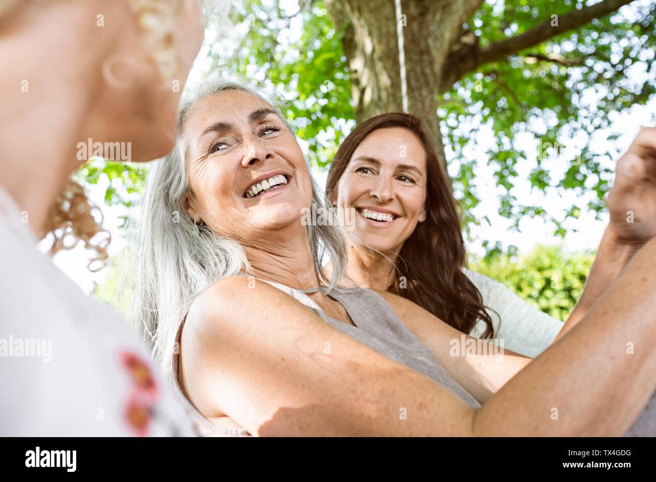 Le donne di una famiglia relax nel giardino, seduto su un letto di oscillazione Foto Stock