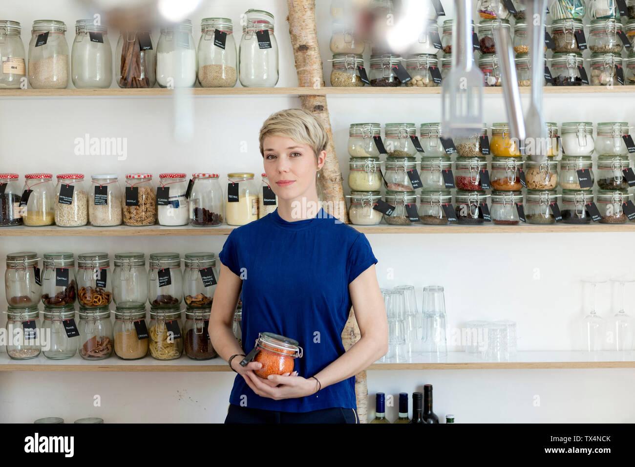 Ritratto di donna vaso di contenimento nella parte anteriore del ripiano di spezie in cucina Foto Stock