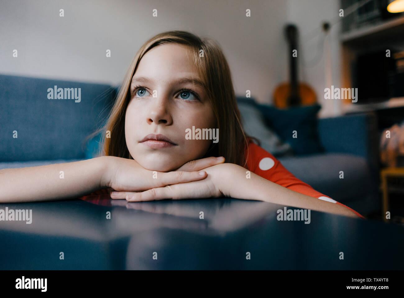Ragazza seria in appoggio la sua testa sul tavolino da caffè a casa Foto Stock
