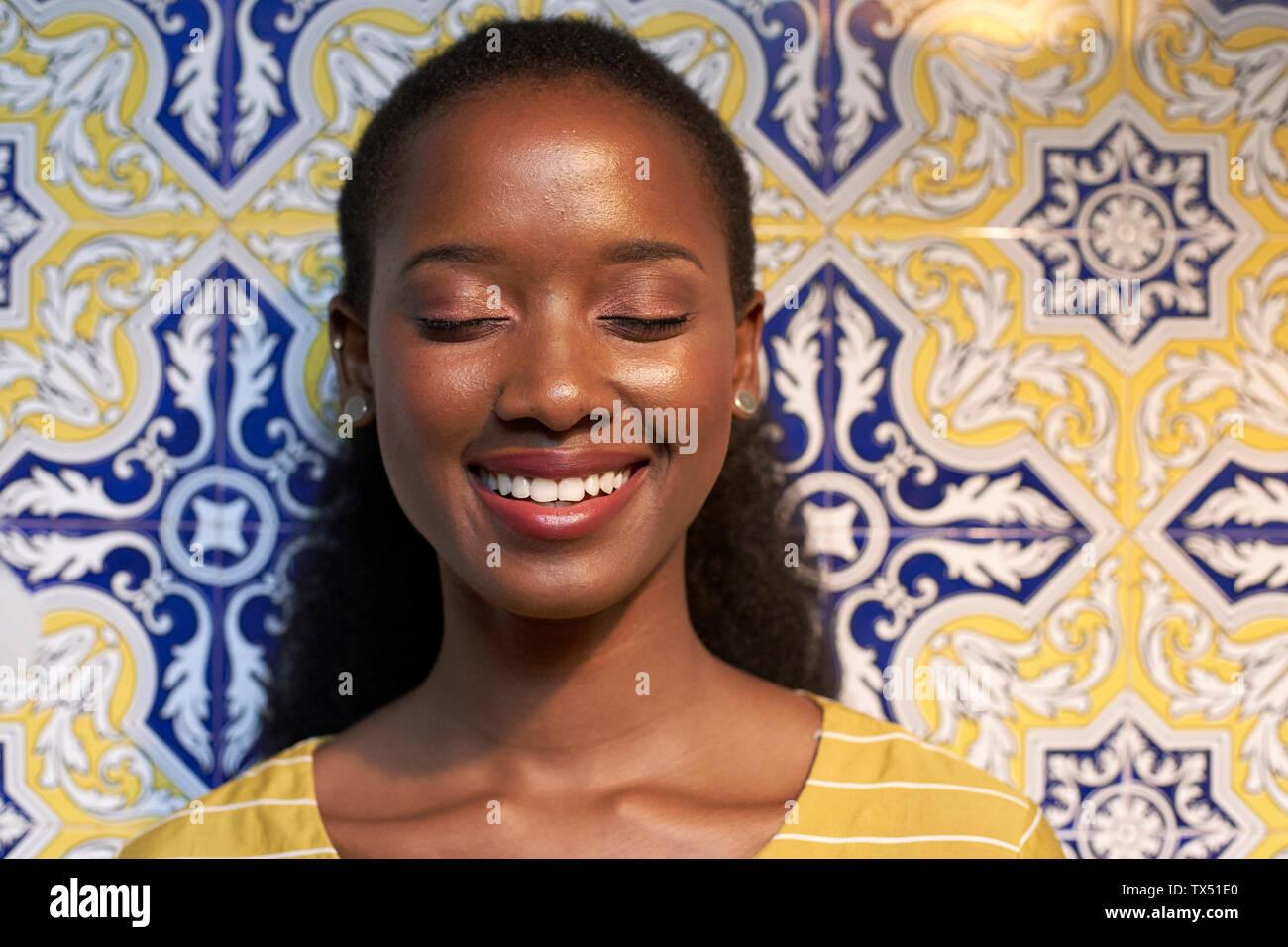 Ritratto di un felice giovane donna in corrispondenza di una parete piastrellata Foto Stock