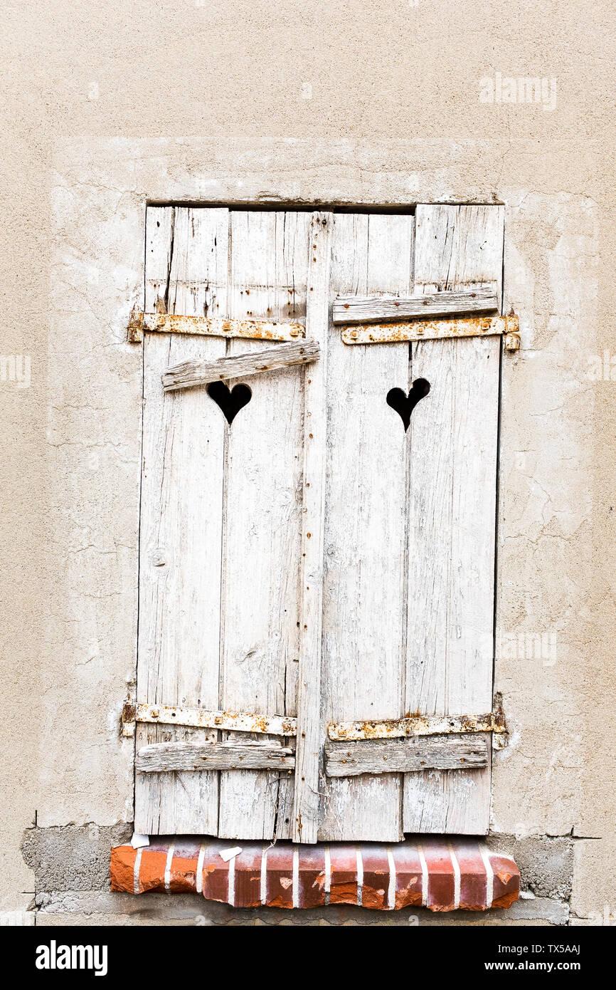 Vecchio weathered grigio ante di finestre con cuore fori sagomati in antico muro Immagini Stock