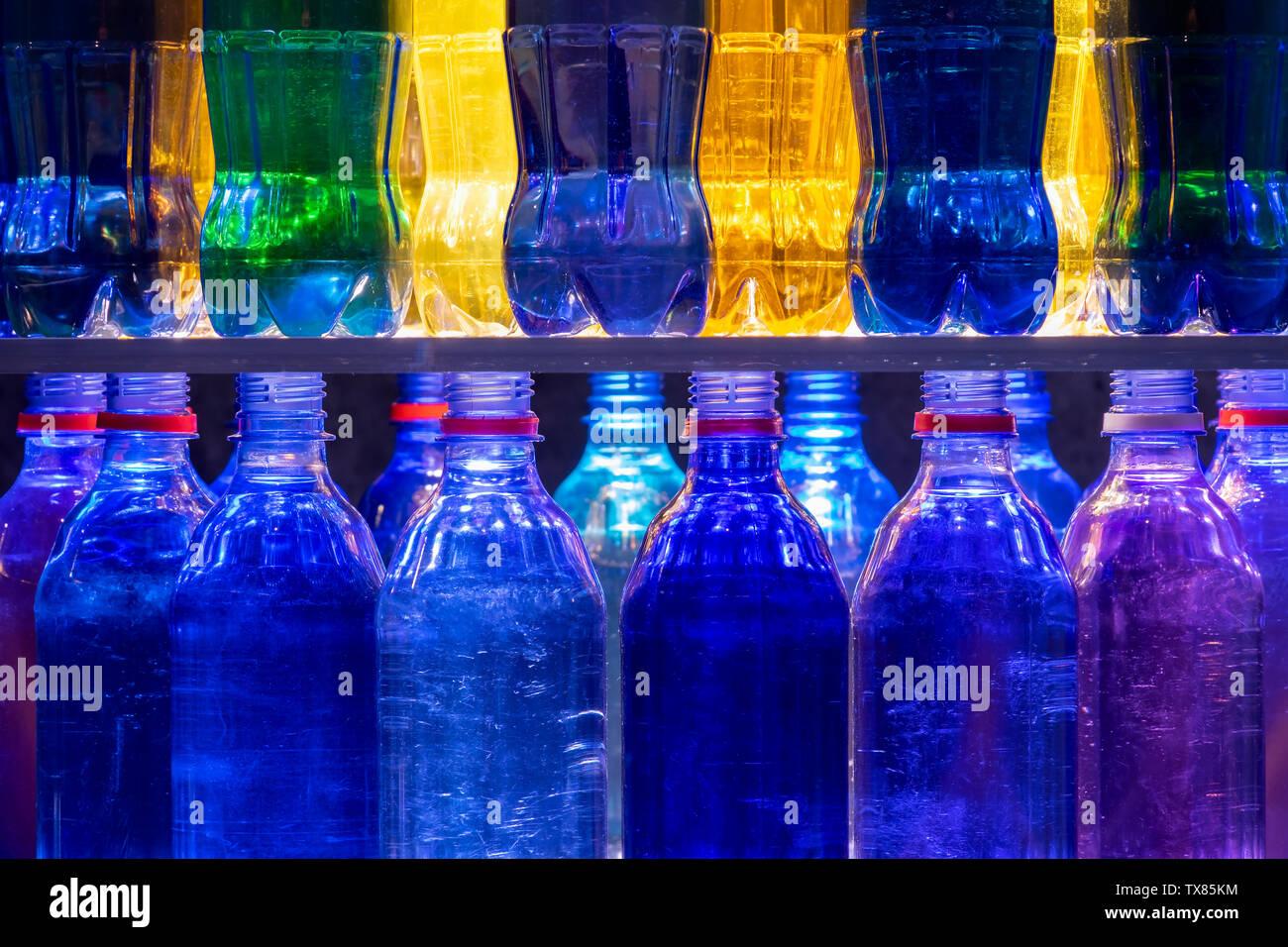 Colorate le bottiglie di plastica impilate su ripiani Immagini Stock