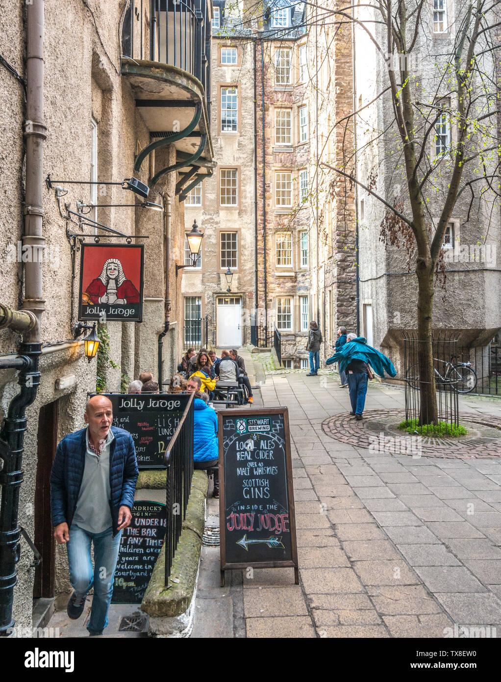 Il Jolly giudice pub, con gente seduta ai tavoli esterni in un cortile di multipiano stone tenement edifici, nella Vecchia Edimburgo, Scozia, Regno Unito. Immagini Stock