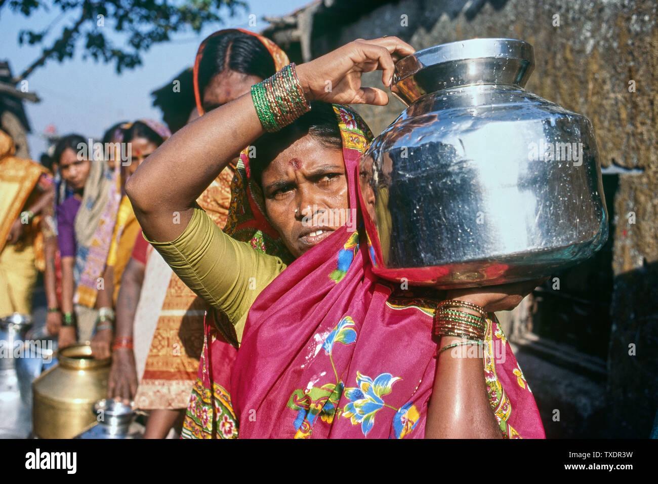 Le donne in piedi in coda per raccogliere acqua in baraccopoli, Mumbai, Maharashtra, India, Asia Immagini Stock