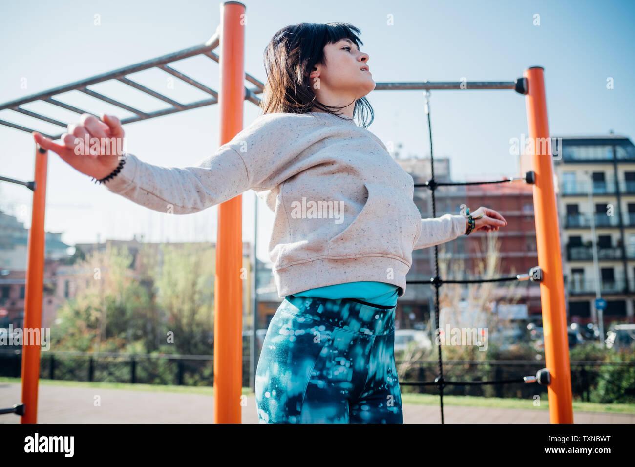 Classe Calisthenics presso palestra all'aperto, giovane donna salta con le braccia aperte Foto Stock