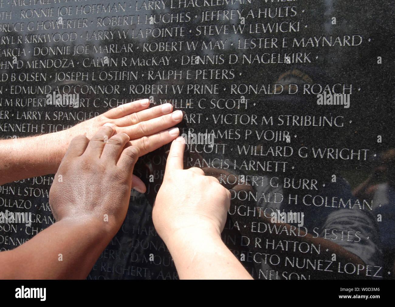 Vietnam Veterans John Broton, Cloise Orand e Leonard 'Doc' Brooks cerca i nomi dei loro compagni caduti, che sono stati uccisi durante un agguato in Vietnam nel 1968, presso il Memoriale dei Veterani del Vietnam a Washington il 29 maggio 2006. (UPI foto/Kevin Dietsch) Immagini Stock