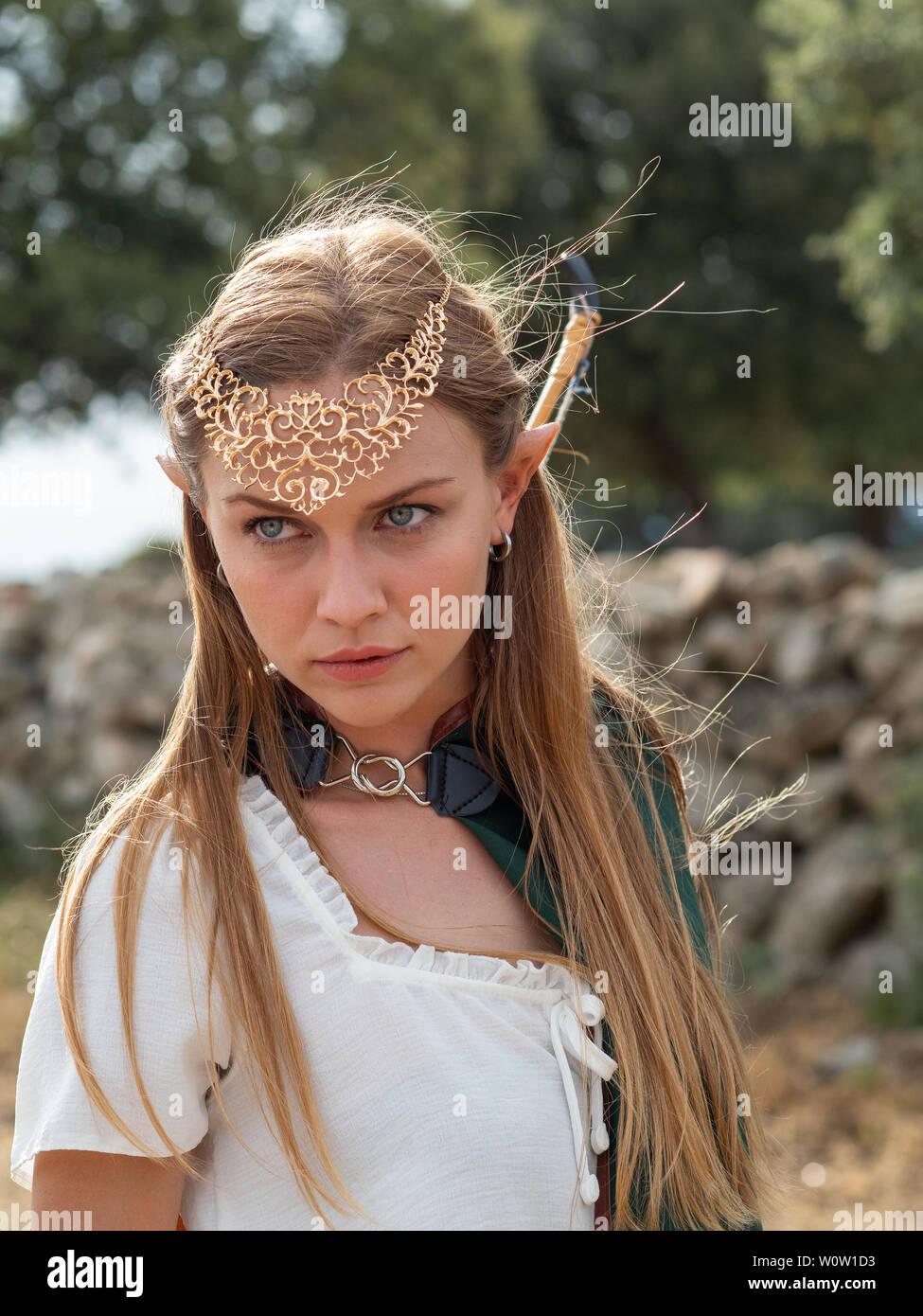 Ragazza bionda con gli occhi blu e il trucco con elf orecchie pone nel campo con un inchino e un capo verde. Immagini Stock