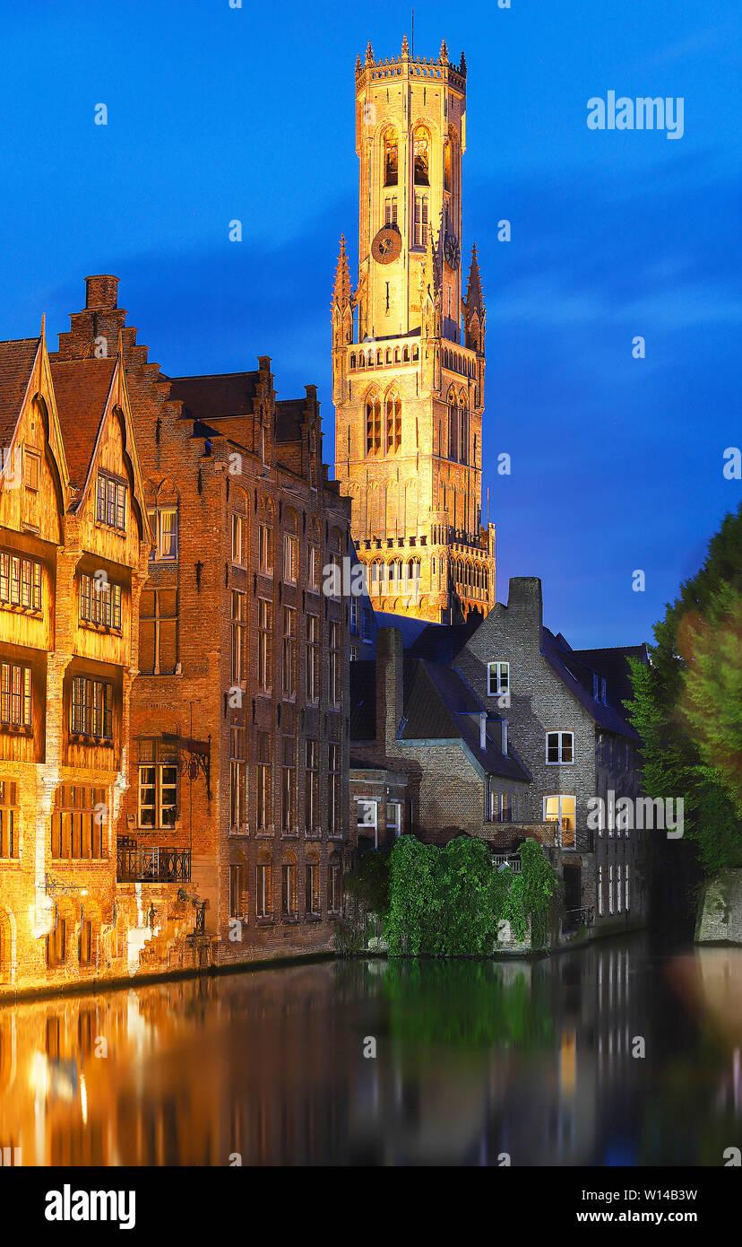 Famosa vista di Bruges turistico attrazione landmark - Rozenhoedkaai canal con la torre campanaria e le vecchie case lungo il canal grande e con albero nella notte. Belgio Foto Stock