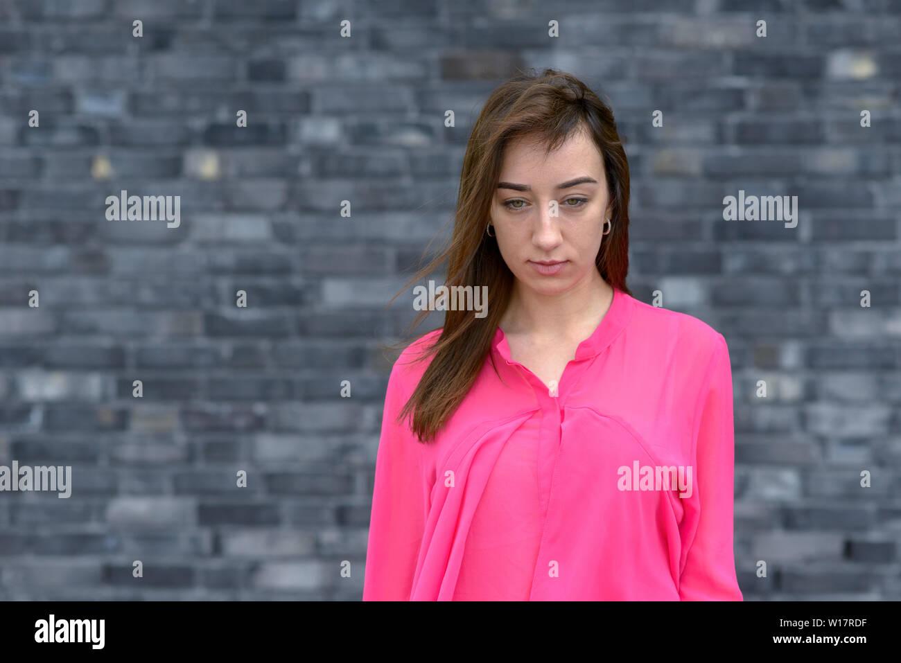 Premurosa donna giovane con abbattuto gli occhi e una espressione seria in posa di un rosa luminoso in alto nella parte anteriore del grigio di un muro di mattoni Immagini Stock